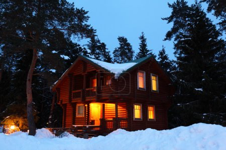 Photo for Wooden house in winter wood in twilight - Royalty Free Image