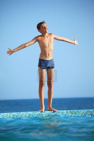 Photo pour Garçon adolescent debout près de la piscine contre la mer, les plantes mains en parties - image libre de droit