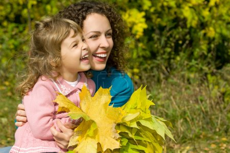 Photo for Young woman and little girl laugh with leaves in hands in garden autumn - Royalty Free Image