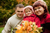 Happy family of three persons in the autumn park