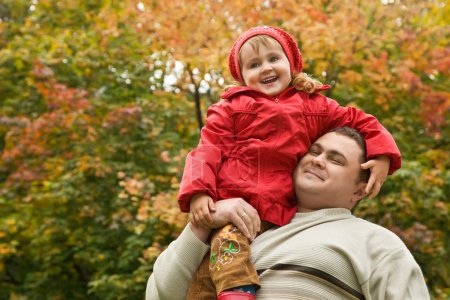 Photo for Little girl sits on shoulder at man In park in autumn - Royalty Free Image
