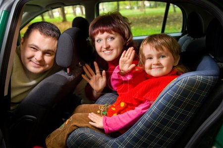 Photo for Married couple and little girl Greeting to wave hands in car in park - Royalty Free Image