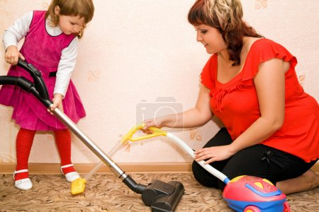 Little Girl and woman vacuum a carpet