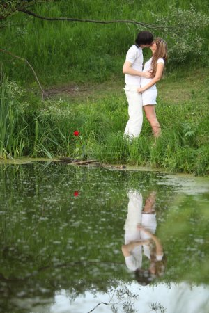 Young pair kisses on bank of pond