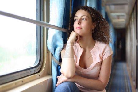 Young woman looks in train window