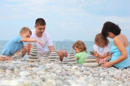 Photo pour Famille avec trois enfants construit pierres piles sur la plage de galets - image libre de droit