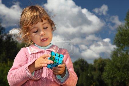 kleines Mädchen mit Zauberwürfel im Sommer draußen