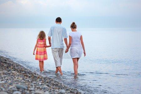 Photo pour Une famille heureuse avec petite fille marcher sur la plage en soirée - image libre de droit