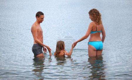 Happy family with little girl bathe in sea, standing back