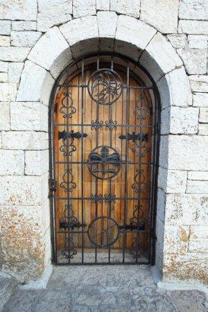 Door behind lattice in stone wall