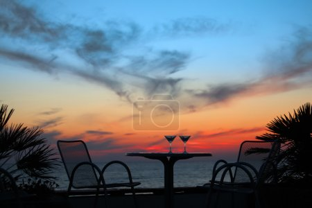 Table with two glasses of wine on sunset on sea outdoor