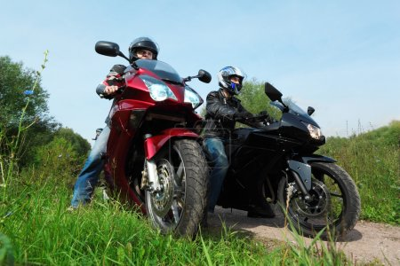 Two motorcyclists standing on country road, bottom view