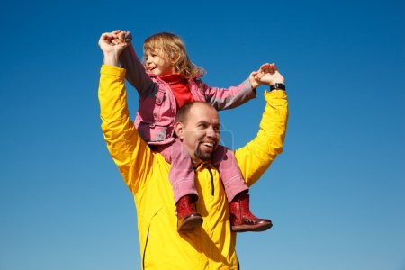 Cheerful little girl sits on shoulders at man
