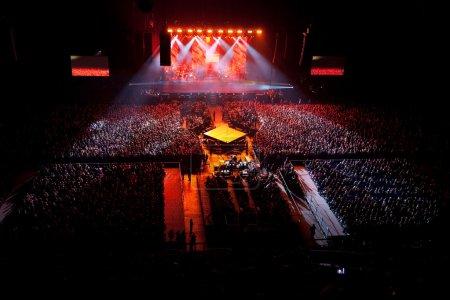 Photo pour Concert spectacle musical. un rouge. spectacle de lumière. le chanteur de groupe groupe est faisant une danse sur scène. lumières au-dessus de scène. - image libre de droit