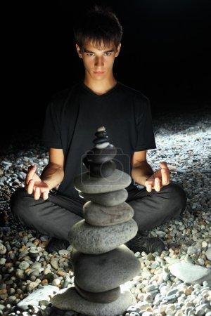 Teenager boy meditating near pyramid from pebble on stony seacoa