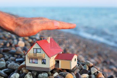 Photo pour Maquette de maison avec garage sur plage pierreuse en soirée, main d'homme sur maison - image libre de droit