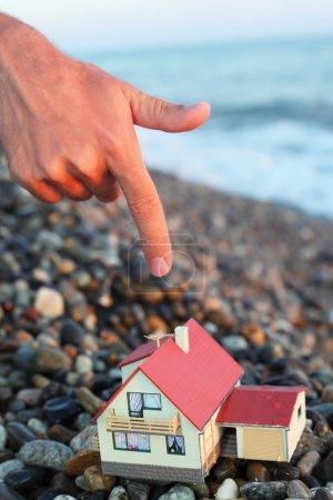 Photo pour Maquette de maison avec garage sur plage pierreuse en soirée, main d'homme avec index sur maison - image libre de droit