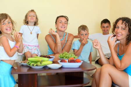 Big happy family with children eats fruit in cosy room