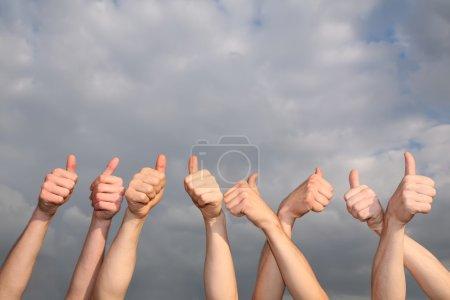 Photo pour Mains avec les pouces levés sur le fond du ciel nuageux - image libre de droit