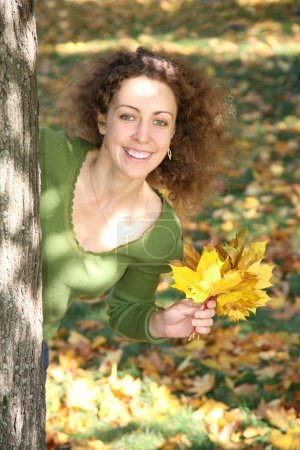 Woman with the yellow leaf looks of the tree
