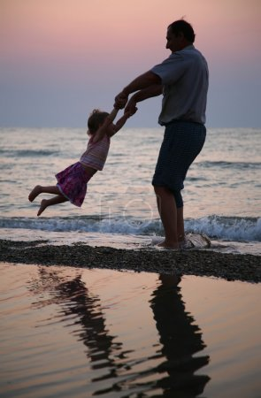 Grandfather rotates child on sunset at sea