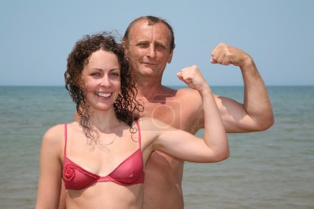 Father and daughter show bicepses