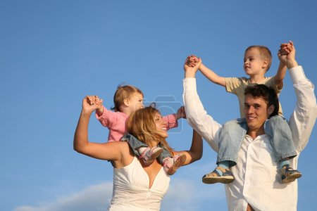 Photo for Father and mother with the children on the shoulders - Royalty Free Image