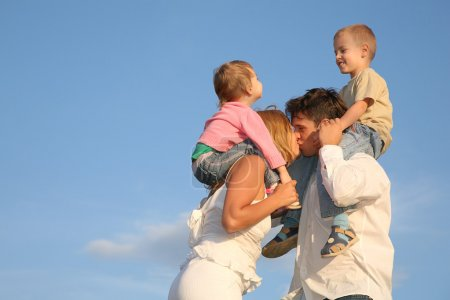 Kissing parents with children on shoulders