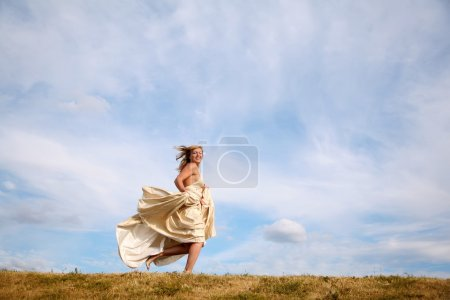 Photo for Young woman in the dress runs along the meadow - Royalty Free Image