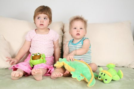 Photo for Two children on sofa with toys - Royalty Free Image