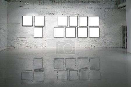Frames on white brick wall and reflections on floor