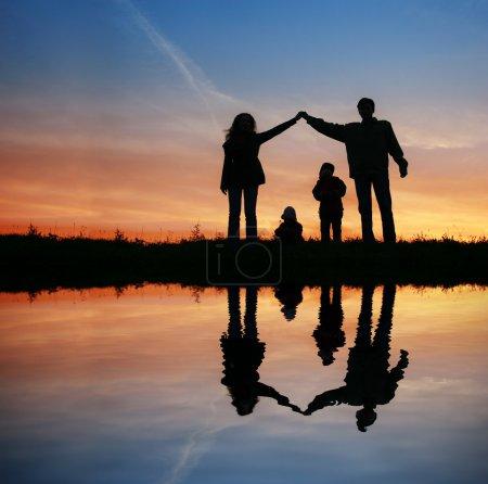 Photo pour Maison familiale de silhouette sur coucher de soleil eau - image libre de droit