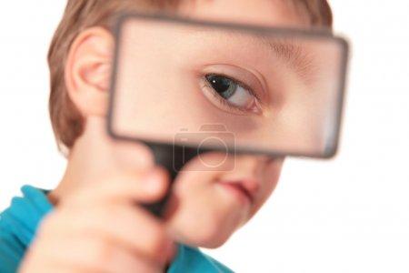 Child looks through magnifier