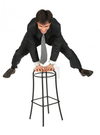 Businessman jumps above stool