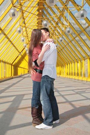 Young pair kisses on footbridge