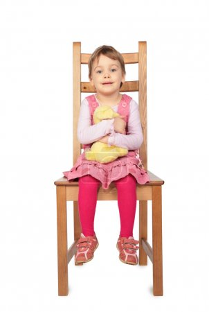 Photo for Girl with toy sitting on stool - Royalty Free Image