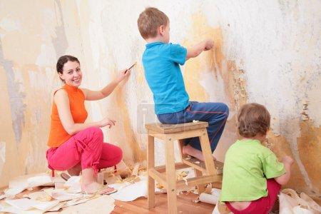Photo pour Enfants aider mère enlever les vieux fonds d'écran - image libre de droit