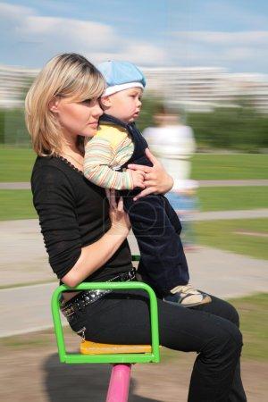 Photo pour Mère et fils sur carrousel - image libre de droit