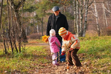 Grand-dad with grandsons in forest in autumn