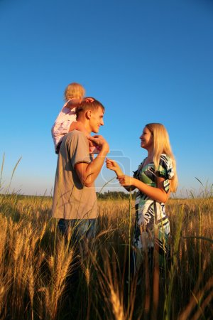 Mother and father with child on shoulders on wheaten field