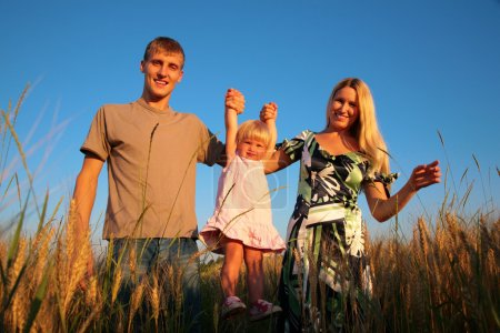 Paretns hold daughter from hands on wheaten field