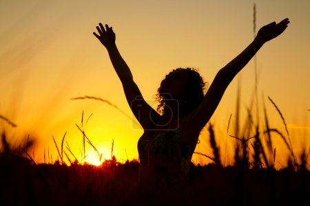 Female silhouette on sunset on wheaten field