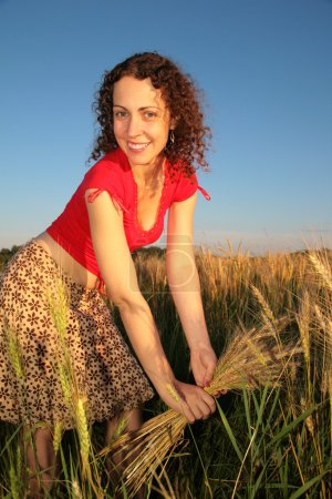 Young woman with earns on wheaten field