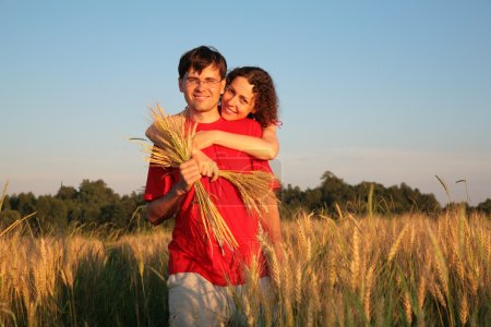 Young woman embraces man behind on wheaten field