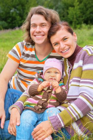 Mother, baby and father sit on grass
