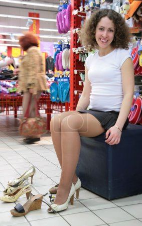 Young woman fitting shoes in shop