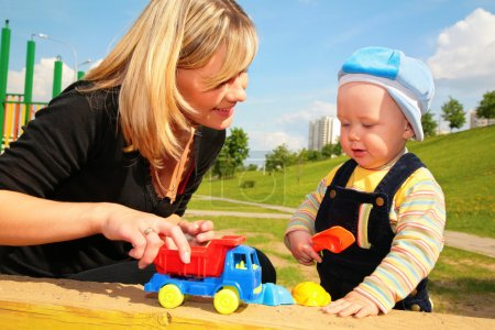 Mother plays with child with toy car