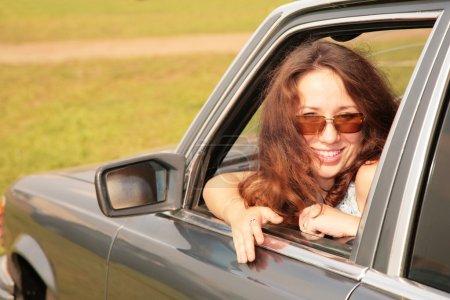 Photo pour Femme sourit après avoir tourné le dos à une fenêtre de la voiture - image libre de droit