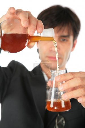 Scientist pours brown liquid from one flask in another