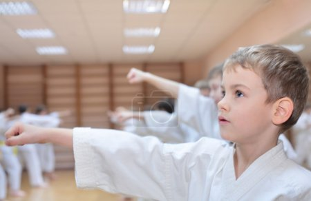 Photo for Boy in sports hall is engaged in karate - Royalty Free Image